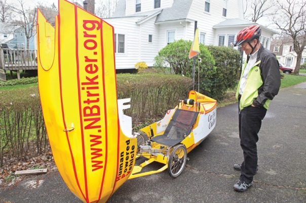 Merrill Gay with his home-built recumbent tricycle, velomobile's hood opened in his driveway in New Britain. Gay's blog address, where he posts his latest velomobile exploits, is prominantly displayed. (4/22/09)